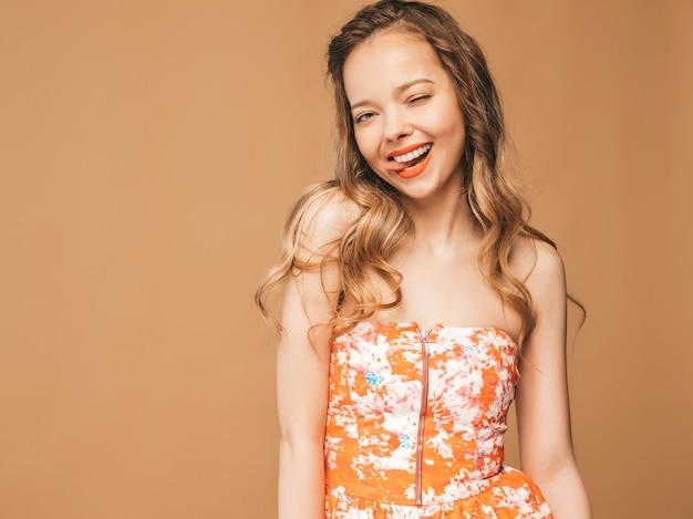 Porträt des schönen lächelnden netten modells mit den rosa lippen. mädchen im bunten sommerkleid. vorbildliche aufstellung. zeigen ihrer zunge