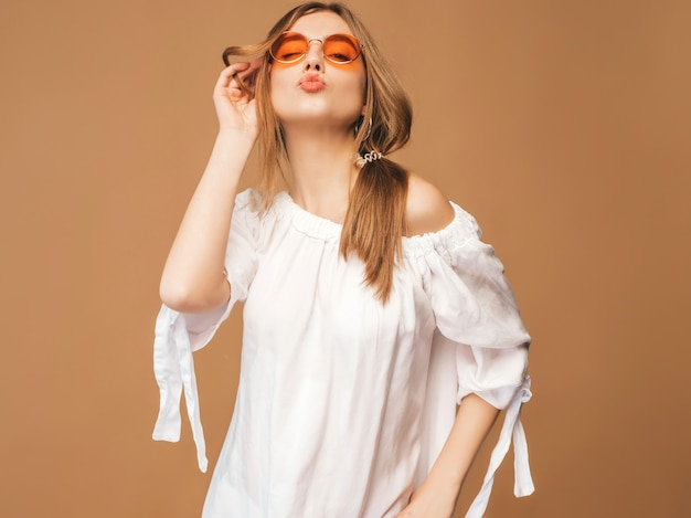 Porträt des schönen lächelnden netten modells mit den rosa lippen. mädchen im weißen sommerkleid. model posiert in sonnenbrille. kuss geben