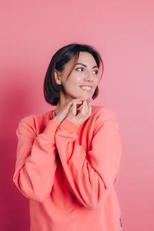 Porträt des schönen lächelnden niedlichen brünetten frauenmodells in lässiger pfirsichpulloverkleidung mit hellem make-up und rosa lippen lokalisiert