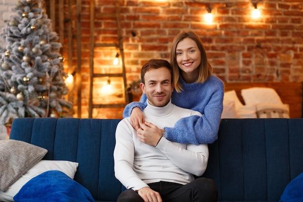 Porträt des schönen lächelnden paares, das an weihnachten umarmt