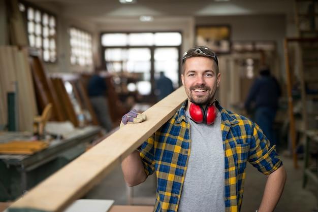 Porträt des schönen lächelnden zimmermanns mit holzmaterial an werkstatt