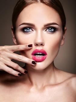 Porträt des schönen mädchenmodells mit abendmake-up und romantischer frisur. sie berührte ihre roten lippen
