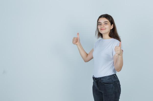Porträt des schönen mädchens, das daumen oben in t-shirt, jeans zeigt und selbstbewusst schaut, vorderansicht