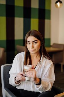 Porträt des schönen mädchens, das heißen tee oder kaffee in einem café mit ihrem handy trinkt.