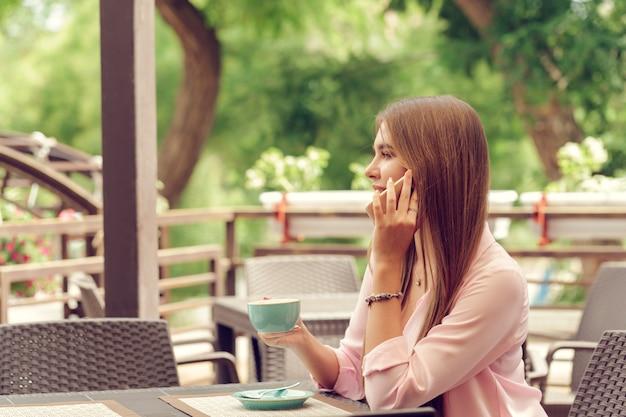 Porträt des schönen mädchens, das ihren handy im café verwendet.