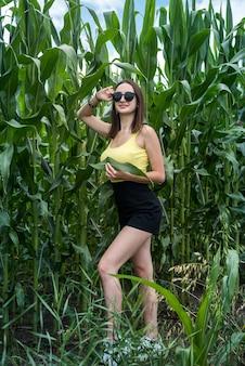 Porträt des schönen mädchens, das im grünen maisfeld aufwirft, genießen sie sommerfreizeit