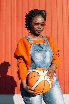 Porträt des schönen mädchens, das mit basketballball aufwirft