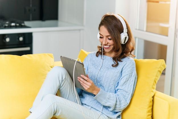 Porträt des schönen mädchens, das musik mit tablette auf sofa zu hause hört.