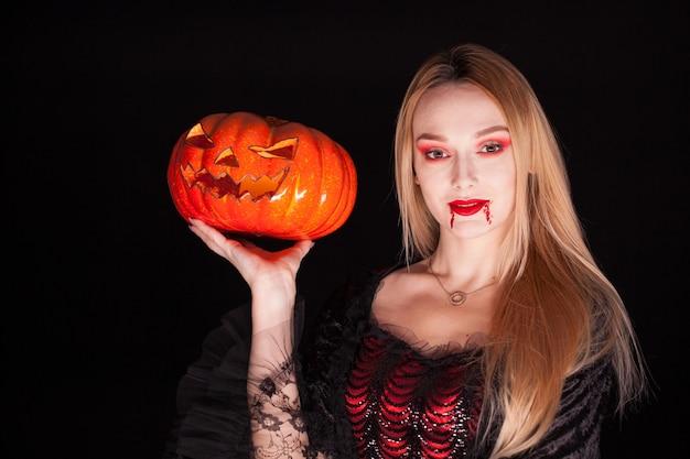 Porträt des schönen mädchens, das wie ein vampir verkleidet ist, der einen kürbis für halloween hält.