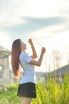Porträt des schönen mädchens der asiatischen oder thailändischen studentenuniversitätsuniform entspannen und lächeln