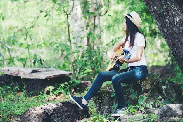 Porträt des schönen mädchens die gitarre mit dem schreiben an der natur spielend