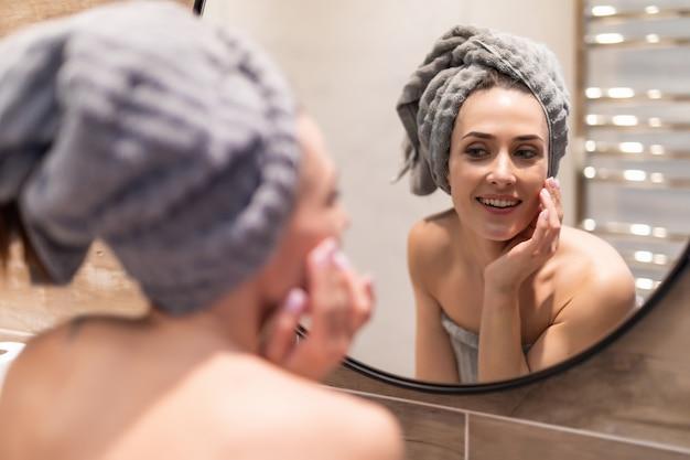 Porträt des schönen mädchens im bademantel und mit handtuch auf dem kopf, das ihr gesicht im badezimmer reinigt