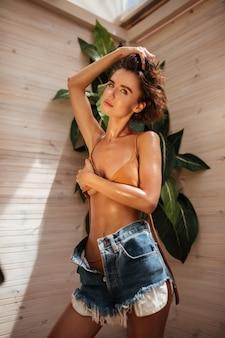 Porträt des schönen mädchens im beige bikini und in den jeansshorts, die auf holzwand mit großen grünen blättern stehen. junge hübsche dame, die verträumt schaut, während sie ihre brust mit händen bedeckt