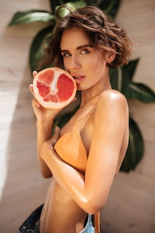Porträt des schönen mädchens im beige bikini und in den jeansshorts, die nachdenklich schauen und die hälfte der grapefruit nahe ihren lippen halten. junges nettes mädchen, das mit grapefruit steht