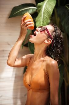 Porträt des schönen mädchens im beigen bikini und in der sonnenbrille, die grapefruitsaft mit der hand stehen und quetschen. junges hübsches mädchen mit der hälfte der grapefruit in der hand