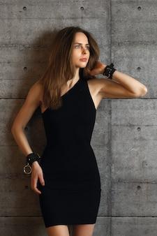 Porträt des schönen mädchens in den schwarzen kleider- und lederhandschellen