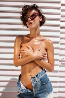 Porträt des schönen mädchens in jeansshorts und sonnenbrille. junges hübsches mädchen, das steht und ihre brust mit händen am strand bedeckt