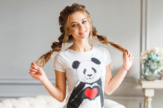 Porträt des schönen mädchens mit braunen augen und dem haar beim zopflächeln
