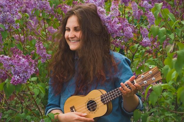 Porträt des schönen mädchens mit dem gelockten haar, welches die ukulele spielt