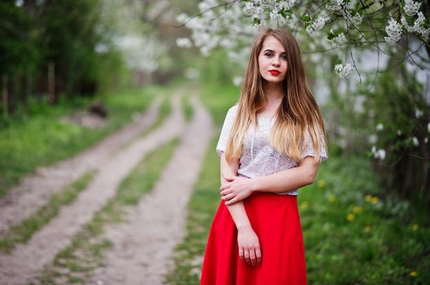 Porträt des schönen mädchens mit den roten lippen am frühlingsblütengarten, tragen auf rotem kleid und weißer bluse.