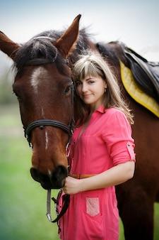 Porträt des schönen mädchens mit einem braunen pferd im park