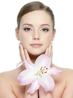 Porträt des schönen mädchens mit lilie nahe ihrem hübschen gesicht mit sauberer haut