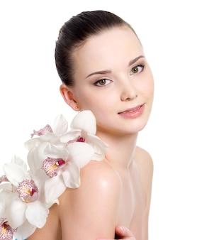 Porträt des schönen mädchens mit sauberer haut und mit blumen - weißer hintergrund