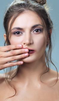 Porträt des schönen mädchens mit sauberer haut und schmierendem lippenstift.