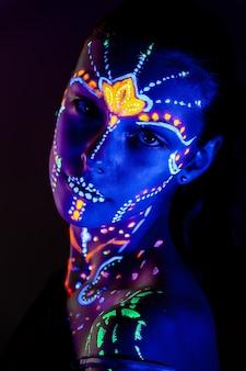 Porträt des schönen mädchens mit ultravioletter farbe auf ihrem gesicht