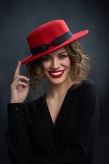 Porträt des schönen mädchens mit wunderbarem lächeln, wering rotem lippenstift und modernem rotem hut.