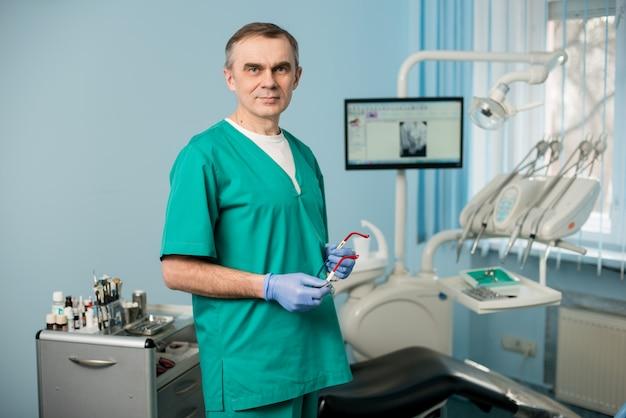 Porträt des schönen männlichen zahnarztes an der morden zahnarztpraxis. zahnheilkunde