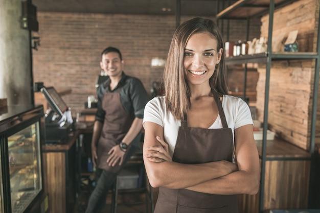 Porträt des schönen mischrassencafébesitzers, der stolz in ihrem geschäft lächelt