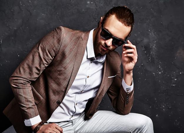 Porträt des schönen mode stilvollen hipster-geschäftsmannmodells gekleidet in elegantem braunem anzug, der nahe dunkelheit sitzt