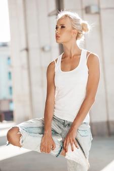 Porträt des schönen netten blonden mädchens im weißen t-shirt und in den jeans, die draußen aufwerfen. nettes mädchen, das auf dem straßenhintergrund steht