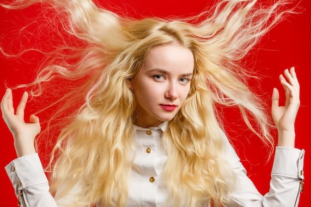 Porträt des schönen netten hauptmädchens mit dem fliegen des gelockten haares