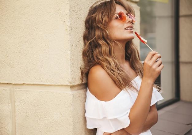 Porträt des schönen niedlichen blonden teenagermodells ohne make-up im sommer hipster weiße kleiderkleidung mit wassermelonensüßigkeit, die nahe gelber wand aufwirft