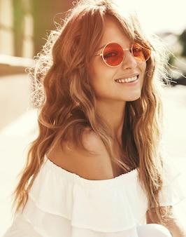 Porträt des schönen niedlichen blonden teenagermodells ohne make-up in den weißen kleidungsstücken des sommer-hipsters, die auf dem straßenhintergrund sitzen