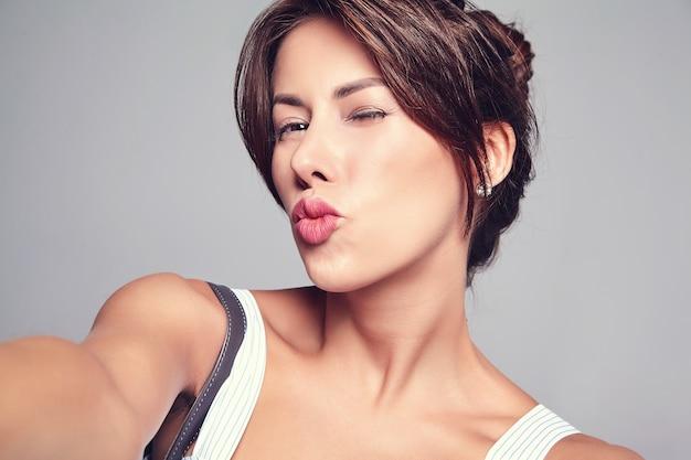 Porträt des schönen niedlichen brünetten frauenmodells im lässigen sommerkleid ohne make-up, das selfie-foto am telefon lokalisiert auf grau mit handtasche macht. luftkuss geben