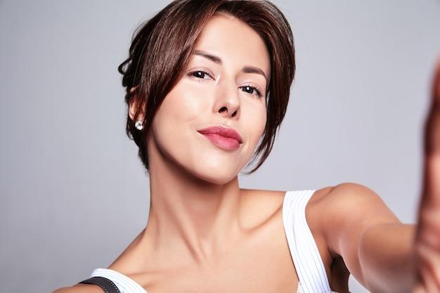 Porträt des schönen niedlichen brünetten frauenmodells im lässigen sommerkleid ohne make-up, das selfie-foto am telefon lokalisiert auf grau mit handtasche macht