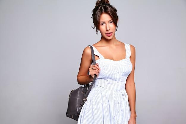 Porträt des schönen niedlichen brünetten frauenmodells im lässigen sommerkleid ohne make-up lokalisiert auf grau mit handtasche