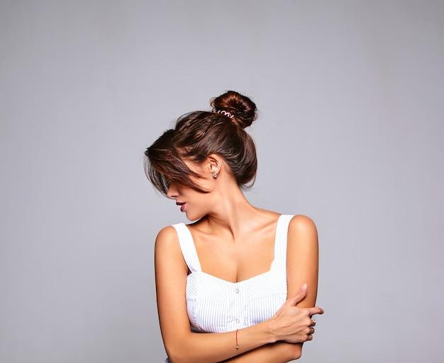 Porträt des schönen niedlichen brünetten frauenmodells im lässigen sommerkleid ohne make-up lokalisiert auf grau