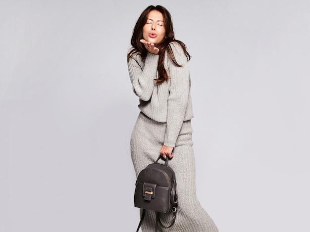 Porträt des schönen niedlichen brünetten frauenmodells in der lässigen herbstgrauen pulloverkleidung ohne make-up lokalisiert auf grau mit handtasche. einen kuss geben