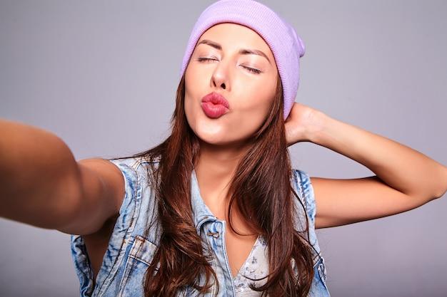 Porträt des schönen niedlichen brünetten frauenmodells in der lässigen sommerjeanskleidung ohne make-up in der lila mütze, die selfie-foto am telefon lokalisiert auf grau macht. luftkuss geben