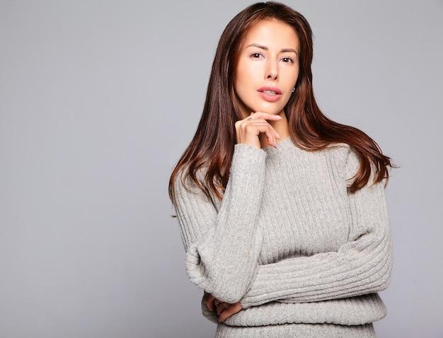 Porträt des schönen niedlichen brünetten frauenmodells in lässiger herbstgrauer pulloverkleidung ohne make-up lokalisiert auf grau
