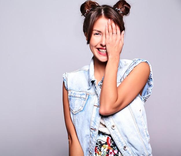 Porträt des schönen niedlichen brünetten frauenmodells in lässiger sommerjeanskleidung ohne make-up mit hörnerfrisur lokalisiert auf grau. bedeckte ihr gesicht mit der hand