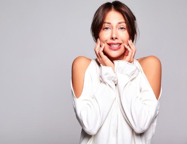 Porträt des schönen niedlichen brünetten frauenmodells in lässiger sommerkleidung ohne make-up lokalisiert auf grau