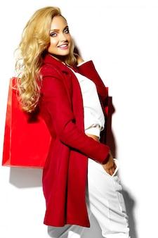 Porträt des schönen niedlichen glücklichen süßen lächelnden blonden frauenmädchens, das in ihren händen große einkaufstasche in den roten hipster-kleidern lokalisiert auf weiß hält