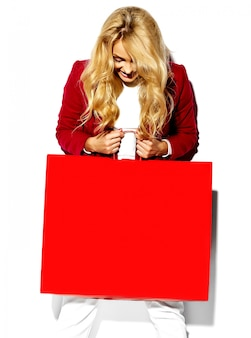Porträt des schönen niedlichen glücklichen süßen überraschten blonden frauenmädchens, das in ihren händen große einkaufstasche in den hippen roten kleidern lokalisiert auf weiß hält