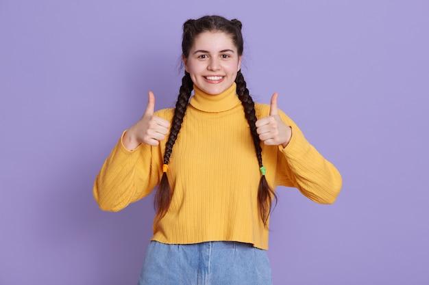 Porträt des schönen niedlichen mädchens, das mit zopffrisur im gelben hemd steht