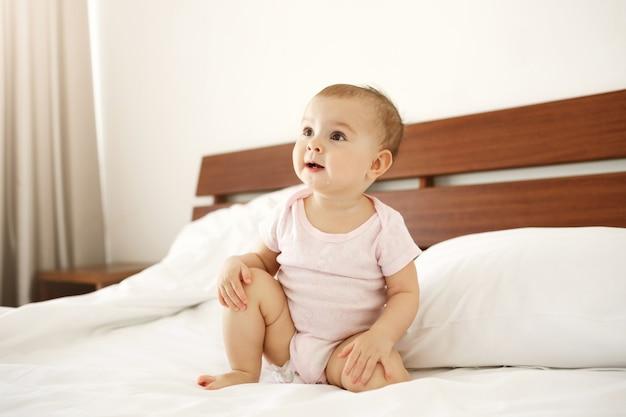 Porträt des schönen niedlichen netten neugeborenen im rosa hemd, das auf bett zu hause sitzt.